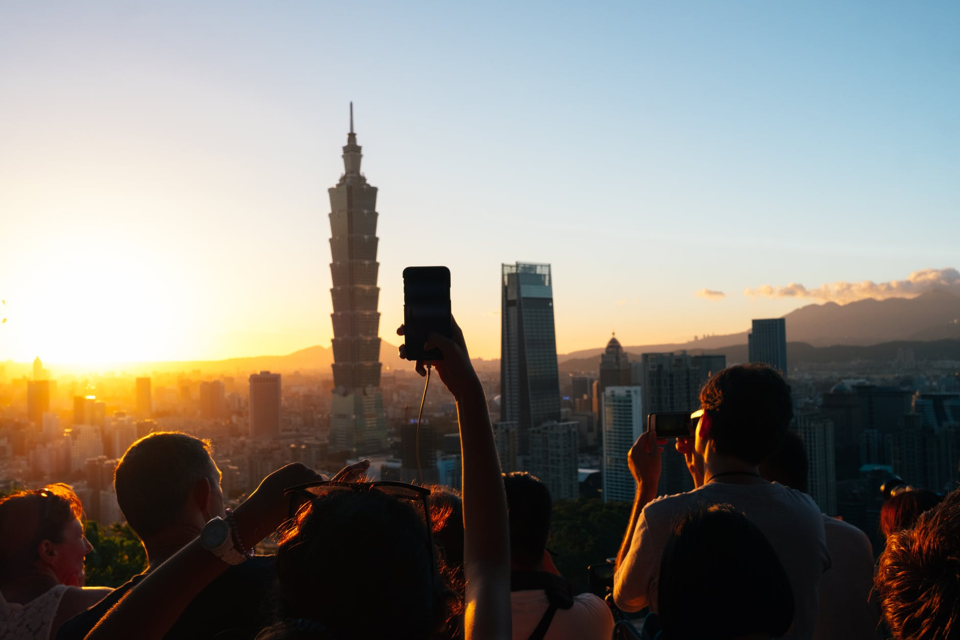 people taking photos of high rise buildings